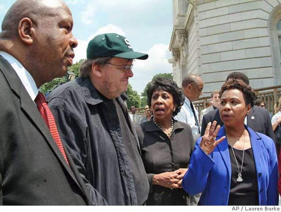 "Michael Moore, director, ""Farenheit 9/11,"" second from left, meets with members of the Congressional Black Caucus on Capitol Hill Thursday, June 24, 2004 prior to a news conference Moore was praised for his movies' exposure of what the caucus calls President Bush's propaganda machine. From left are, Caucus Chairman, Rep. Elijah Cummings, D-Md., Morre, Rep. Maxine Waters, D-Calif., and Rep. barbara Lee, D-Calif. (AP Photo/Lauren Burke) Photo: LAUREN BURKE"