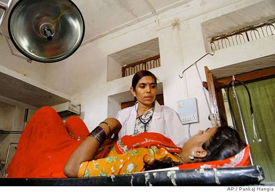 **SPECIAL FOR SAN FRANCISCO CHRONICLE** Dr. Kirti Iyengar examines a patient at the Action Research & Training for Health(ARTH) clinic at Kuncholi village 65 kilometers (41 miles) northwest of Udaipur, Saturday, July 3, 2004. (AP Photo/Pankaj Nangia) Photo: PANKAJ NANGIA