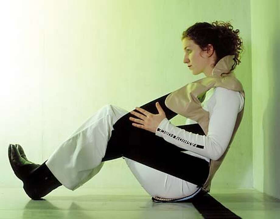 """Clothes As Furniture: Lisa Besset sits in Fashion Force's """"Wearable Chair, 2002,"""" in SFMOMA's """"Body Design"""" exhibit. Photo courtesy of SFMOMA"""