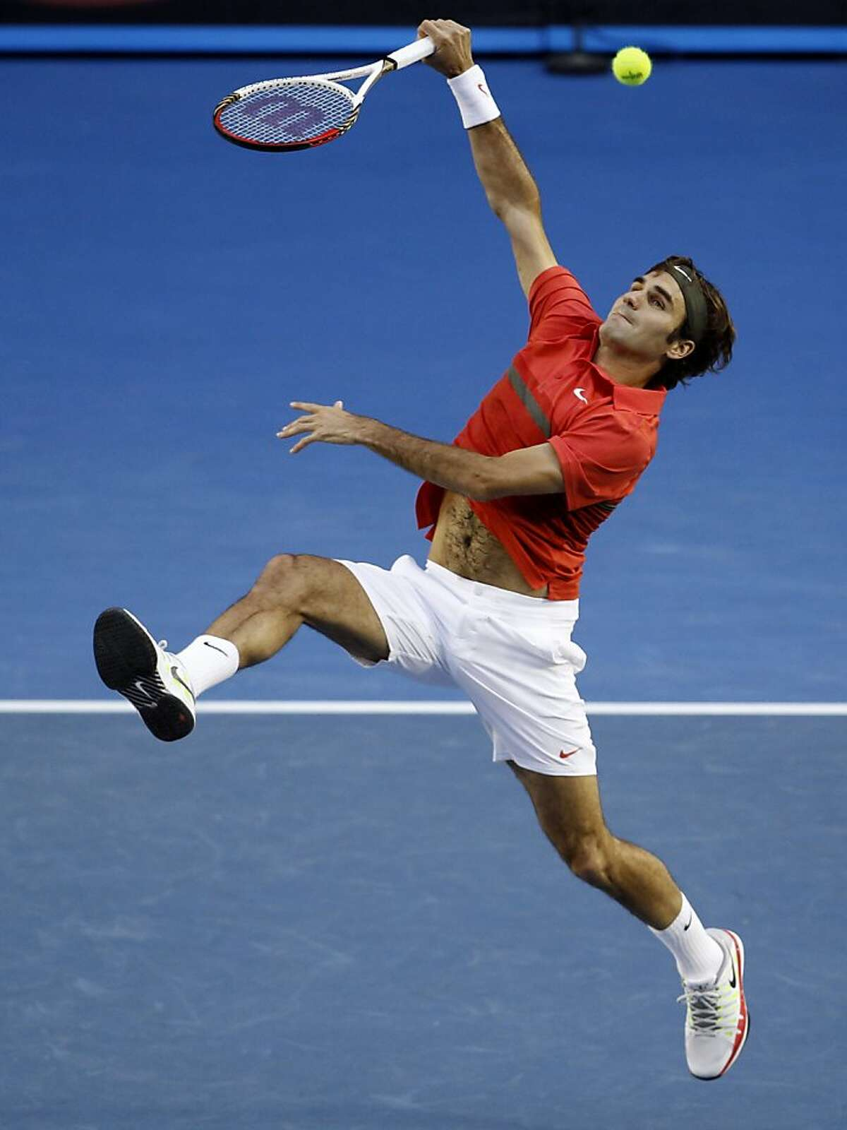 Roger Federer of Switzerland leaps for a smash against Rafael Nadal of Spain during their semifinal at the Australian Open tennis championship, in Melbourne, Australia, Thursday, Jan. 26, 2012. (AP Photo/Aaron Favila)