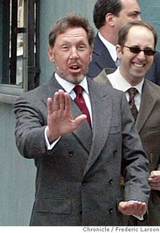 ORACLE_013_fl.jpg; Oracle CEO Larry Ellison directs safety skills to a group of photopraphers as he crosses Larkin at Turk Street before enting the San Francisco Federal Court House to testify for the on going Oracle antitrust. 6/30/04  San Francisco Chronicle Frederic Larson Photo: Frederic Larson
