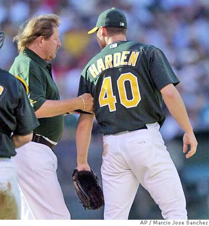 Oakland Athletics starter Rich Harden (40) gets his shoulder checked by trainer Larry Davis after falling while running to first base for a relay in the third innning Saturday, June 26, 2004, in Oakland, Calif. Harden left the game after the play. (AP Photo/Marcio Jose Sanchez) Photo: MARCIO JOSE SANCHEZ
