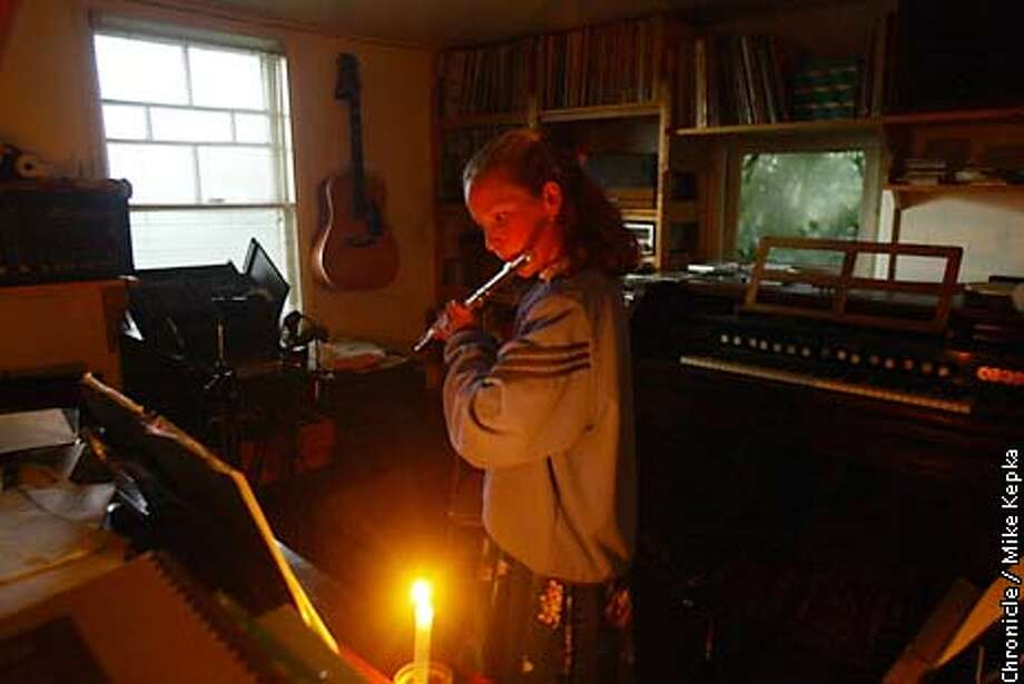 Liz Reid-Wainscoat, 11, has been practicing her flute by candle light in her Ben Lomond home since the power went out on her block Saturday. BY MIKE KEPKA/THE CHORNICLE Photo: MIKE KEPKA