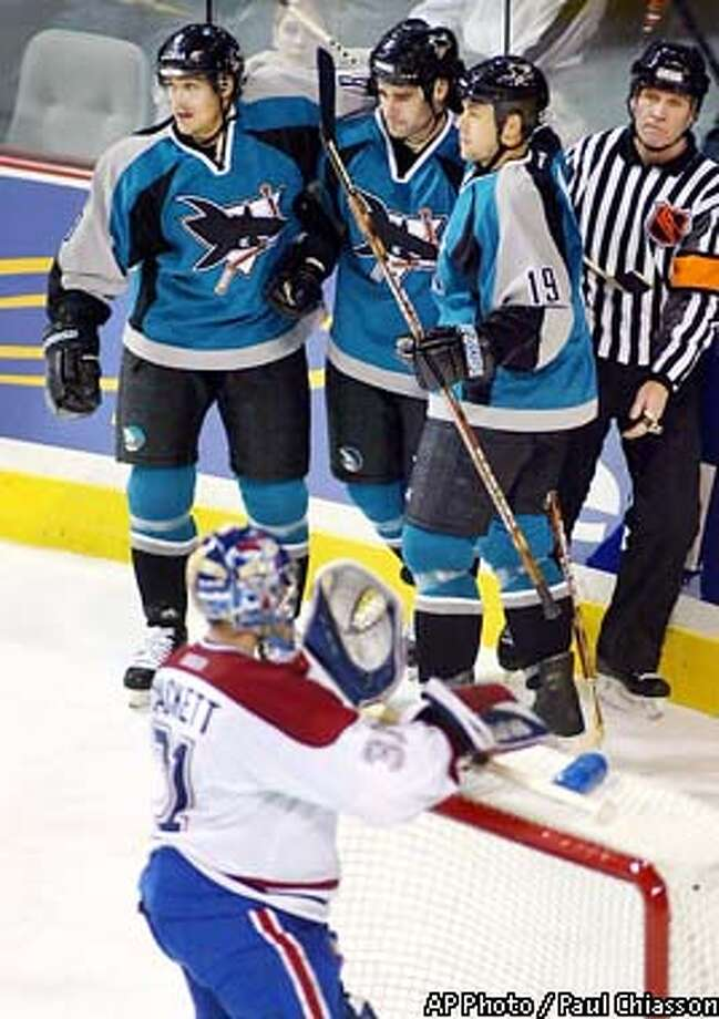 San Jose Sharks' Teemu Selanne. left, is congratulated by teammates Patrick Marleau, center, and Marco Sturm after scoring past Montreal Canadiens goaltender Jeff Hackett during third period NHL action Tuesday, Dec. 17, 2002, in Montreal. The Sharks beat the Canadiens, 3-1. (AP Photo/Paul Chiasson) Photo: PAUL CHIASSON