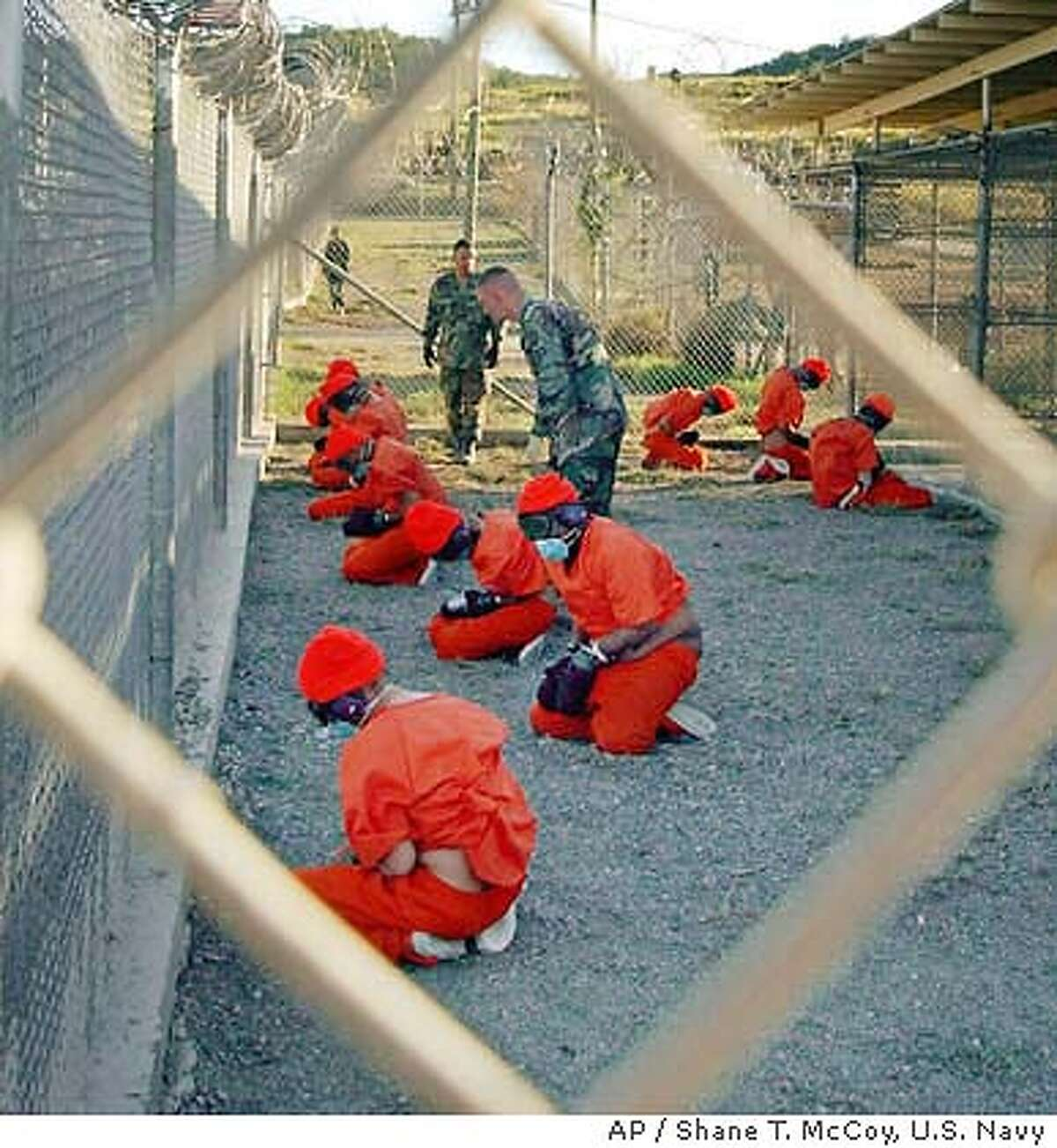 ** FILE ** Taliban and al-Qaida detainees sit in a holding area at Camp X-Ray at Guantanamo Bay, Cuba, during in-processing to the temporary detention facility in this Jan. 11, 2002 file photo. Controversy over prisoner abuse at U.S.-run prisons in Iraq and Afghanistan has left the Guantanamo Bay, Cuba, detention facility for terrorist suspects largely untouched. but that may soon change. A senior Navy admiral who briefly visited Guantanamo Bay in early May has recommended a more in depth look at how prisoners were treated there. (AP Photo/U.S. Navy, Shane T.McCoy)
