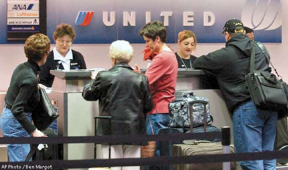 ticket agents assist passengers Monday, Dec. 9, 2002, at San Francisco International airport in San Francisco. UAL, the nation's No. 2 air carrier, filed for bankruptcy protection Monday. (AP Photo / Ben Margot) Photo: BEN MARGOT