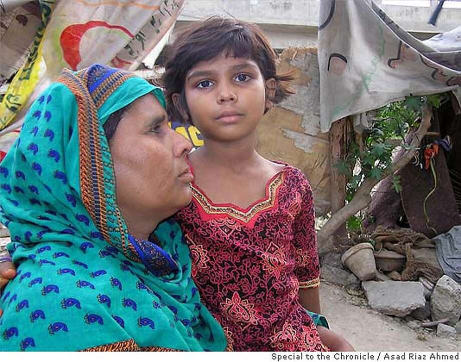 Perveen Barkat and her daughter Sharee Komal stand outside their hut in a low income area in the eastern Pakistani city of Lahore. The seven year old Sharee was lured away from home and raped by a nieghbor May 29 in a case that has led some Pakistanis to call for rapists being charged under Pakistan's Anti-Terrorism Laws.  Asad Riaz Ahmed  PHOTO BY ASAD RIAZ AHMED/SPECIAL FOR THE CHRONICLE