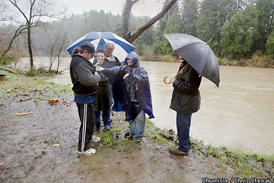 Residents of the River Bend RV Resort and Campground monitor the water level of the Russian River next to their trailor park near Rio Nido in Sonoma County. (L-R) Randy Briney (with cat), Jeana Heutmaker, Gregg Hackett (blue & white umbrella) Linda Smets (blue poncho) and Larry Throop (black umbrella). The river crested earlier in the day, but continued rain brought the threat of flooding. BY CHRIS STEWART/THE CHRONICLE Photo: CHRIS STEWART