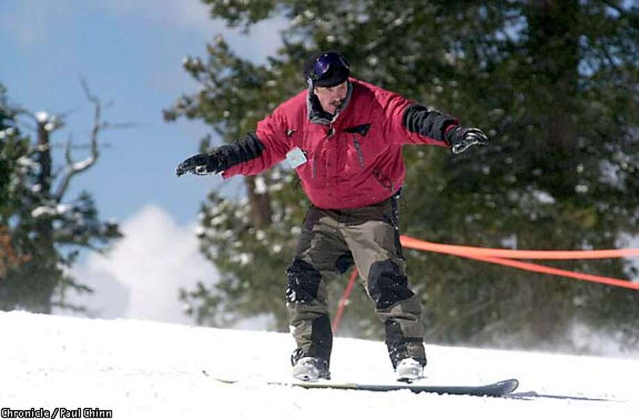 Slip-sliding away: The author makes his stand atop a snowboard. Chronicle photo by Paul Chinn