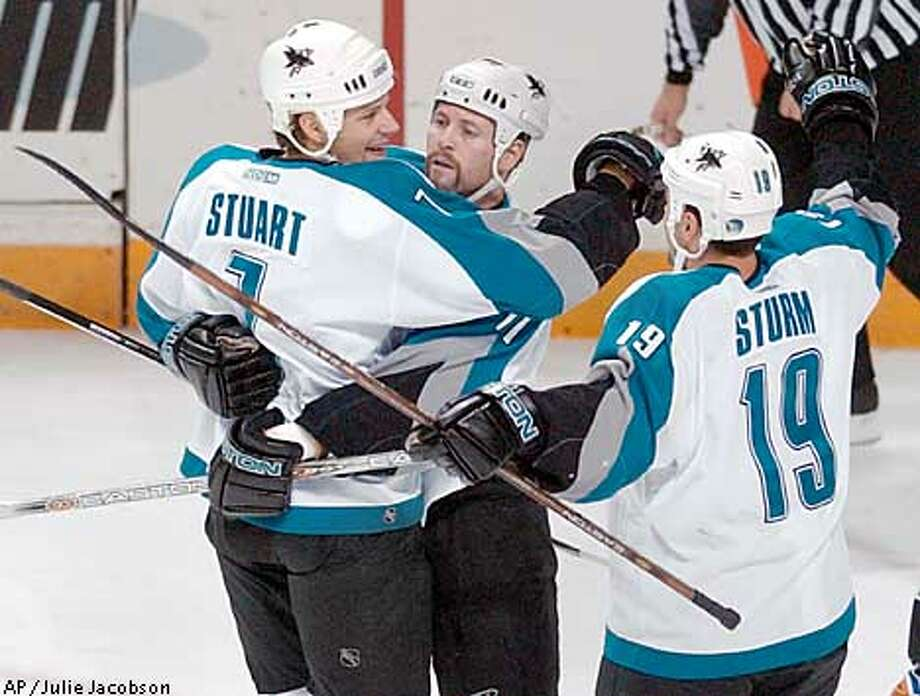 San Jose Sharks' Brad Stuart, left, is congratulated by Owen Nolan, of N. Ireland, center, and Marco Sturm, of Germany, after scoring against the Washington Capitals during the first period in San Jose, Calif., Saturday, Dec. 14, 2002. (AP Photo/Julie Jacobson) Photo: JULIE JACOBSON