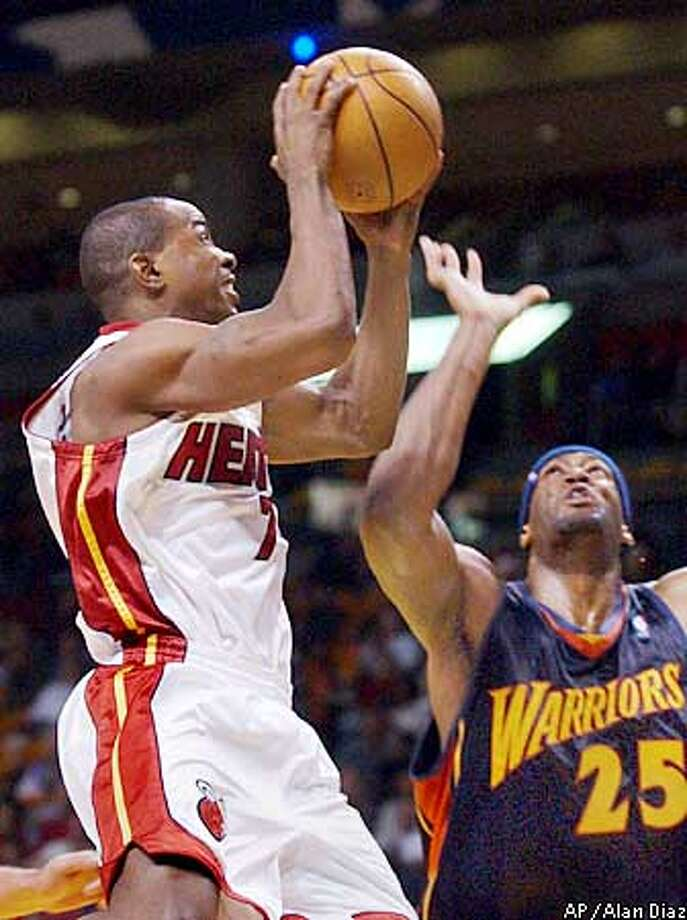 Miami Heat's Mike James, left, scores over Golden State Warriors' Erick Dampier (25), in the second quarter, Saturday, Dec. 14, 2002 at the American Airlines Arena in Miami. (AP Photo/Alan Diaz) Photo: ALAN DIAZ