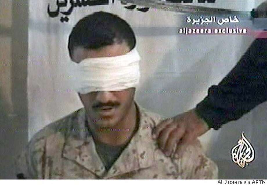 This image from a video broadcast by the Al-Jazeera network Sunday June 27 2004 shows a man identified as on the video as a U.S. Marine who Iraqi militants claim to have lured from his base and captured. There was no immediate comment from miltary sources but a military identity card and other documents were also shown. (AP Photo/Al-Jazeera via APTN)