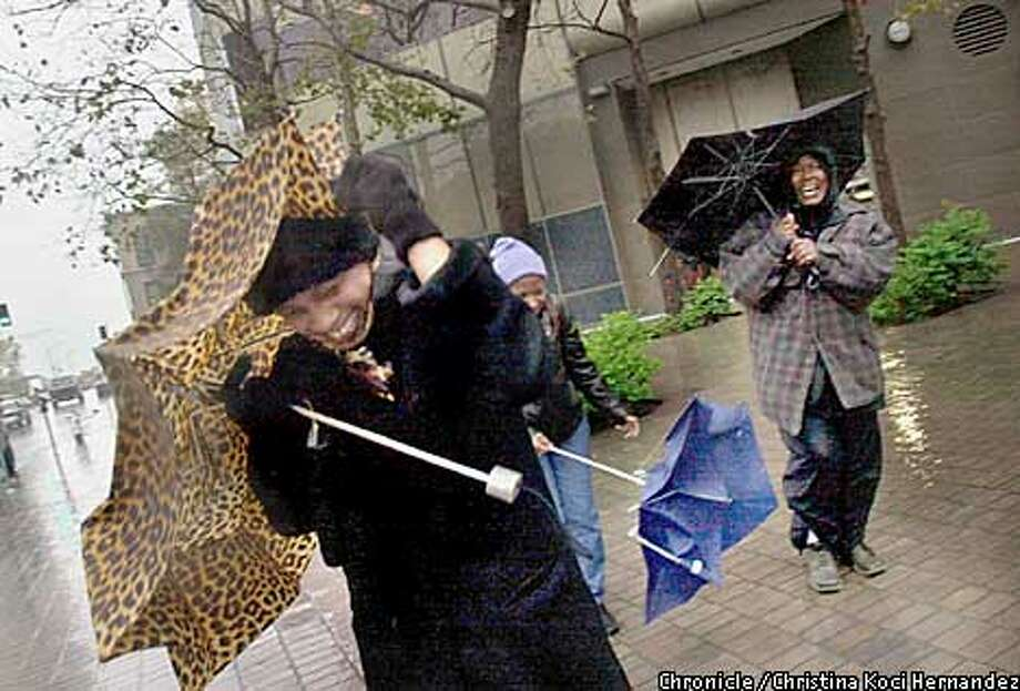 CHRISTINA KOCI HERNANDEZ/CHRONICLE  (L) Dolores Roberts and ,far right, Linda Wilson, both workers at the Federal Building, brave the storm on Broadway at 12th St. in downtown Oakland. Rain in downtown Oakland. Photo: CHRISTINA KOCI HERNANDEZ