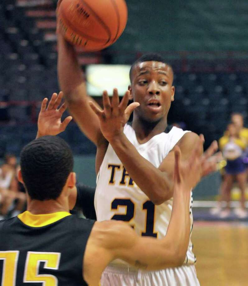 Troy's #21 Isiah Dobere passes the ball around Henniger High's #15 Tommie Spinner, left, during Saturday's game at the  Times Union Center in Albany Dec. 31, 2011.  (John Carl D'Annibale / Times Union) Photo: John Carl D'Annibale / 00015915A
