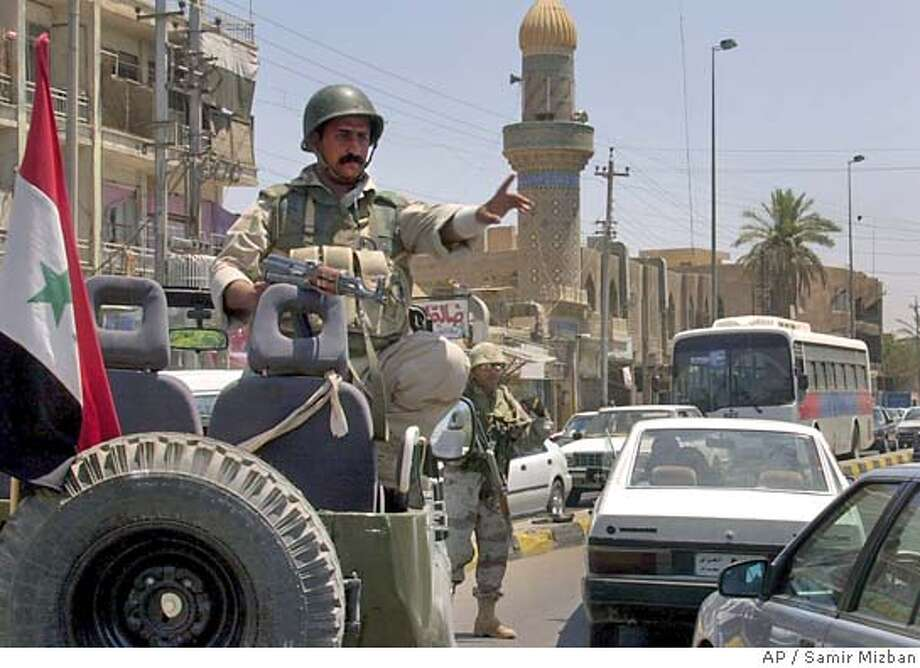 Members of the Iraqi Civil Defense Corps divert traffic in Baghdad, Iraq, Saturday, June 26, 2004. Extra forces have been called onto the streets in advance of the handover of national sovereignty at the end of the month. (AP Photo/Samir Mizban) Photo: SAMIR MIZBAN