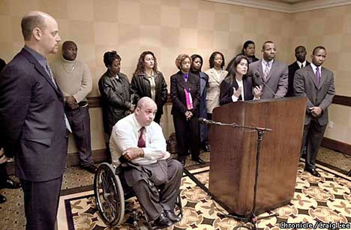 35 employees filing a huge class action suit against Fed Ex. Photo of Rosa Olmos-Benyshek, a Fed Ex employee at the San Jose Airport, speaking at the press conference. The lawyers surrounding her are Todd Schneider (far laft), Guy Wallace (wheelchair), Waukeen McCoy (right of Rosa), and Cael Davis (far right). The other people standing are the Fed Ex employees involved in the suit. Photo by Craig Lee/San Francisco Chronicle