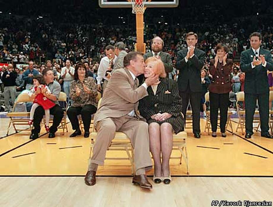 "Los Angeles Lakers' announcer Francis Dayle ""Chick"" Hearn kisses his wife, Marge, during a halftime ceremony honoring his 3,000th consecutive broadcast at the Forum in Inglewood, Calif., Monday, Jan. 19, 1998. (AP Photo/Kevork Djansezian)"