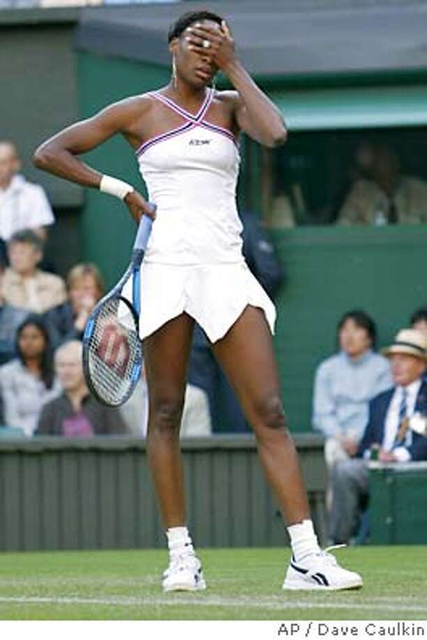 Venus Williams holds her head during her Women's Singles, second round match against Karolina Sprem of Croatia, on the Centre Court at Wimbledon, Thursday June 24, 2004. Sprem defeated Williams 7-6 (5), 7-6 (6).(AP Photo/Dave Caulkin) ** EDITORIAL USE ONLY ** Photo: DAVE CAULKIN