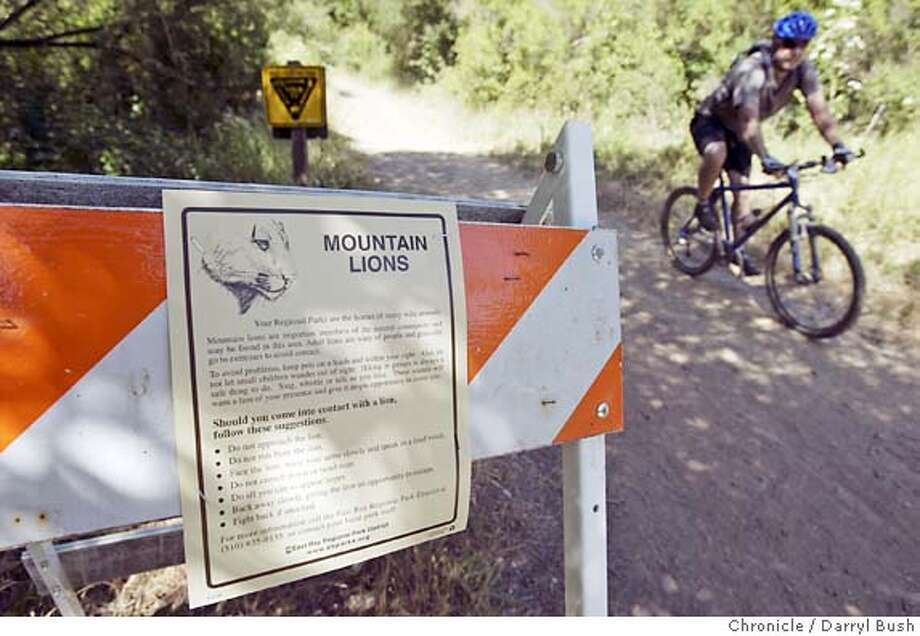 A road sign is posted with a flyer warning of a recent mountain lion sighting at the entrance to Canyon Trail that leads to East Ridge Trail in the Redwood Regional Park of East Bay Regional Park District.  Event on 6/23/04 in Oakland.  Darryl Bush / The Chronicle Photo: Darryl Bush