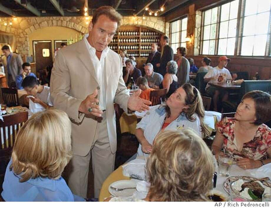 Making a surprise visit, Gov. Arnold Schwarzenegger went table to table asking lunch-time patrons to call their state legislators and tell them to vote for his budget,at a Folsom, Calif. restaurant, Thursday, June 24, 2004. Schwarzenegger told, Pam Chackel, left, Michele Cooksy, Janine Wilson, back second from right, and Grace Milan, right, that he hoped to sign the 2004-05 state budget by the July 1 deadline but couldn't do it unless the legislature passed his spending plan. (AP Photo/Rich Pedroncelli) Photo: RICH PEDRONCELLI