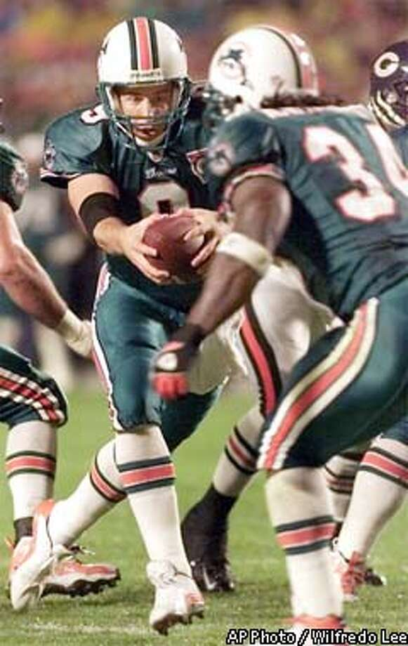Miami Dolphins' quarterback Jay Fiedler, left, hands off to running back Ricky Williams during the first quarter against the Chicago Bears Monday, Dec. 9, 2002, in Miami. (AP Photo/Wilfredo Lee) Photo: WILFREDO LEE