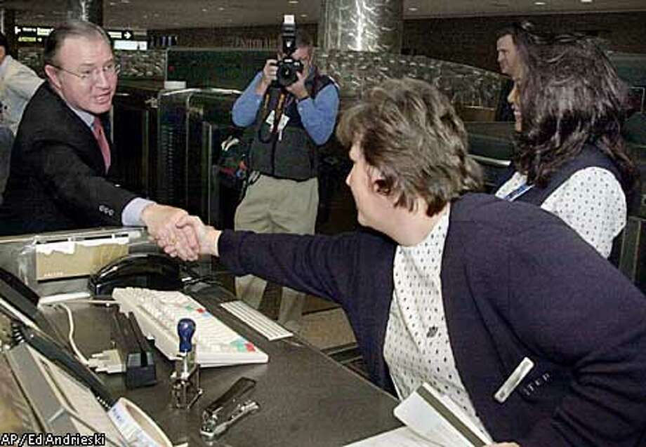 United Airlines CEO Glenn Tilton, left, shakes hands with United ticket agent Kelly Easton at Denver International Airport on Tuesday, Dec. 10, 2002. Tilton held a news conference at the airport, shook hands with employees and passengers and met with United employees. Uniteds filing for Chapter 11 bankruptcy on Monday, the sixth largest by any company and the biggest in aviation history, came less than a week after the federal government rejected a plea for financial assistance. (AP Photo/Ed Andrieski) Photo: ED ANDRIESKI