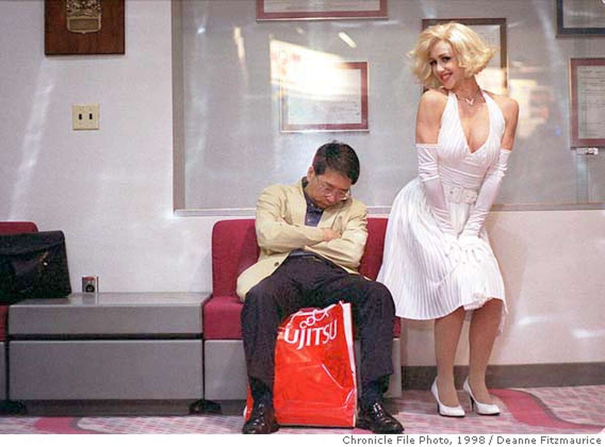 COMDEX19-1/C/17NOV98/BU/DF - Coty Alexander, a Marilyn Monroe impersonater poses next to a conventioneer who fell asleep in the Las Vegas Convention Center after a full day of attending Comdex, a technology convention in Las Vegas. CHRONICLE PHOTO BY DEANNE FITZMAURICE RAN: 11/21/1998 SAT. PAGE B1/BU CAT