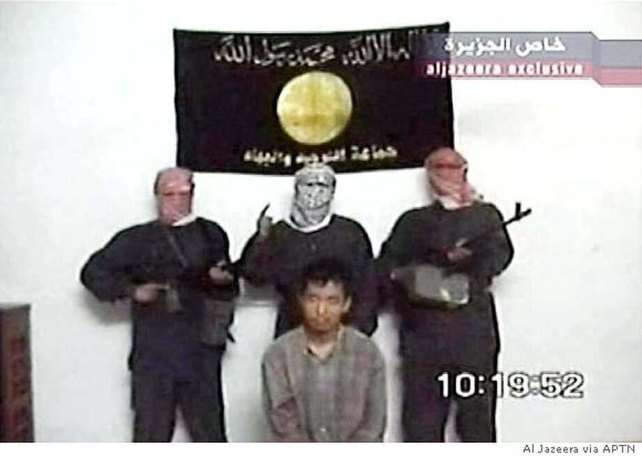 Masked men stand around a South Korean hostage in a videotape aired on Arabic television station Al Jazeera on June 20, 2004. An Iraqi group has threatened to behead the unnamed South Korean hostage if Seoul does not end cooperation with U.S. occupying authorities, one of the men said on the tape. A banner in the background named the group as Jama'at al-Tawhid and Jihad, the name of the militant group led by al Qaeda operative in Iraq Abu Musab al-Zarqawi. South Korea said on Friday it would start to deploy 3,000 troops to Iraq's Arbil area in early August to help rebuild the northern Kurdish region. U.S. OUT GERMANY OUT NO ARCHIVE EDITORIAL USE ONLY REUTERS/Al Jazeera via Reuters Television Photo: HO