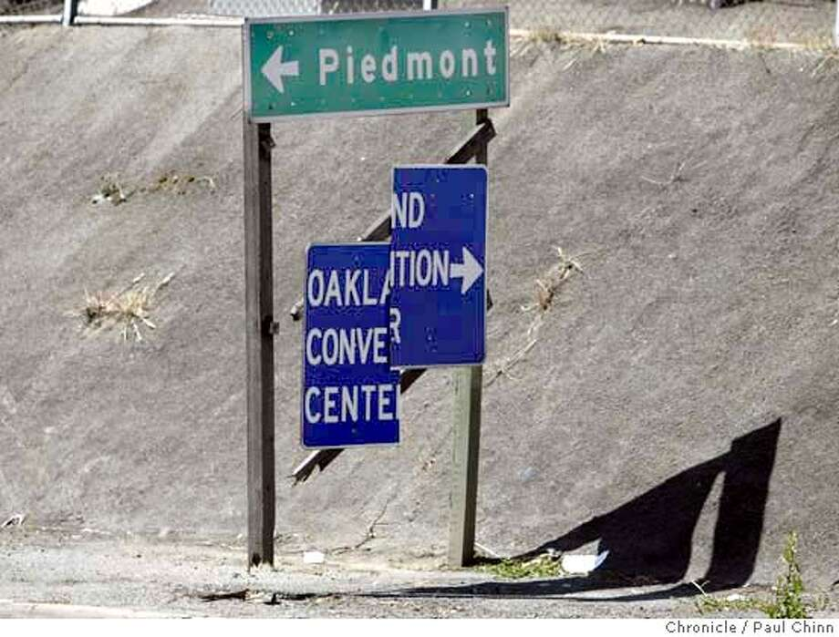 FOR CHRONWATCH: A blue directional sign for the Oakland Convention near the end of the Grand Ave. off ramp of 580 West is broken in half and dangling off its hinge in Alameda on 6/15/04. STAFF/The Chronicle Photo: STAFF