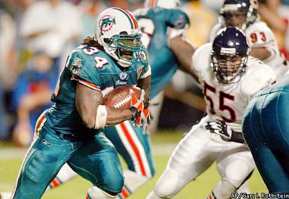 Miami Dolphins running back Ricky Williams (34) slides around Chicago Bears linebacker Mike Caldwell (55) during the first half of the Monday, Dec. 9, 2002, game in Miami. (AP Photo/Gary I. Rothstein) Photo: GARY I. ROTHSTEIN