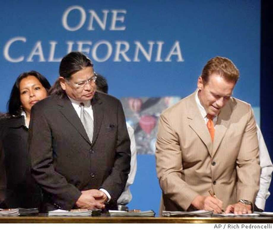 Anthony Pico, chairman of the Viejas Band of Kumeyaay Indians, left, looks on, as Gov. Arnold Schwarzenegger signs an Indian gambling compact with the tribe at a ceremony in Sacramento, Calif., Monday, June 21, 2004. The agreement, reached with five California tribes, allows their tribal casinos to increase the number of slot machines beyond the current 2,000 per tribe cap. In return the tribes will pay the state a licensing fee for each additional slot machine up to $25,000 a machine. The tribes agreed to issue bonds that will bring the state $1 billion to help close this years state budget gap. (AP Photo/Rich Pedroncelli) Photo: RICH PEDRONCELLI