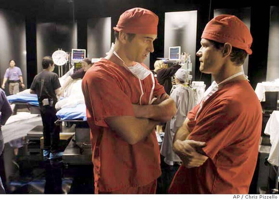 "Actors Julian McMahon, left, and Dylan Walsh, co-stars of the FX series ""Nip/Tuck,"" confer between takes as crew members dress the show's set at Paramount Studios in Los Angeles, June 8, 2004. The series about the two ethically challenged surgeons, portrayed by Walsh and McMahon, begins its second season Tuesday, June 22, 2004 at 10 p.m. EDT. (AP Photo/Chris Pizzello) Photo: CHRIS PIZZELLO"