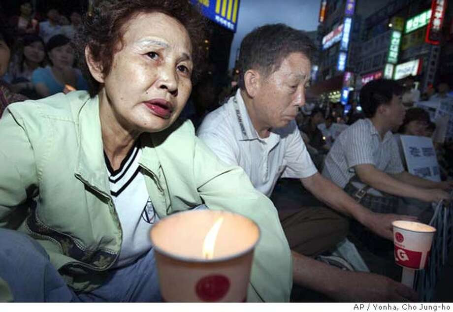 Kim Jong-kyu, left, and Shin Young-ja, parents of Kim Sun-il who was kidnapped in Iraq, participate in a candlelight vigil protesting against their government's decision to send South Korean troops to Iraq, in downtown Pusan, south of Seoul, Monday, June 21, 2004. The Arab satellite TV network Al-Jazeera aired a videotape purportedly from al-Qaida linked militants showing the South Korean hostage begging for his life and pleading with his government to withdraw troops from Iraq. South Korea said Mondayit will go ahead with its plan to send troops to Iraq despite the abduction of Kim. (AP Photo/Yonha, Cho Jung-ho) ** KOREA OUT ** Ran on: 06-22-2004  Kim Jong Kyu (left) and Shin Young Ja, parents of kidnapped Kim Sun Il, participate in a candlelight vigil in Pusan, south of Seoul, protesting South Korea's plans to send 3,000 troops to Iraq. Photo: CHO JUNG-HO