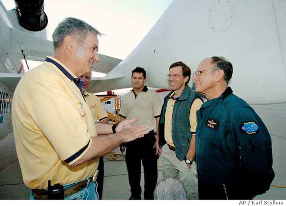 Aerospace engineer Burt Rutan talks with pilot Michael Melvill before he climbs aboard SpaceShipOne for a trip to suborbital space at Mojave, Calif., Monday, June 21, 2004. SpaceShipOne is a privately developed rocket plane that, upon completion of its mission Monday, will become the world's first commercial manned space vehicle and the first non-governmental flight to leave the Earth's atmosphere. (AP Photo/Pool, Karl Stolleis) Photo: KARL STOLLEIS
