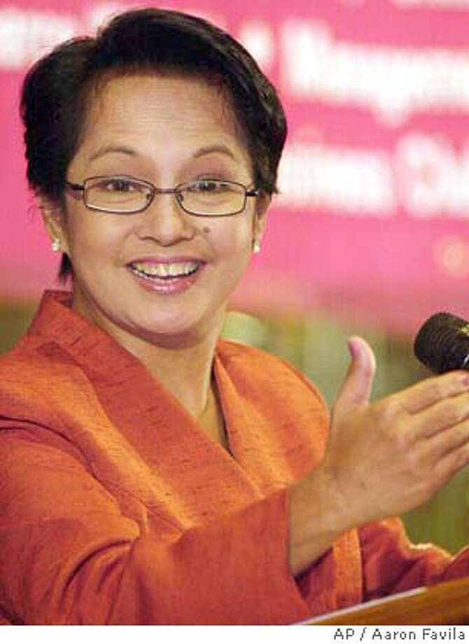 ** FILE ** Philippine President Gloria Macapagal Arroyo gestures as she meets businessmen at the financial district of Makati, south of Manila in this April 14, 2004 file photo. President Gloria Macapagal Arroyo has won another term in office, according to final results Sunday, June 20, 2004, from the May 10 election. (AP Photo/Aaron Favila) APRIL 14 FILE PHOTO Photo: AARON FAVILA