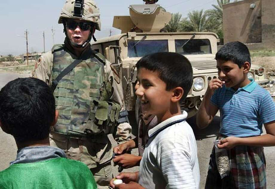 1Sergeant Michael Sell of First Cavalry plays with some Iraqi children in Baghdad, Iraq. Photo: Sherrlyn Borkgren
