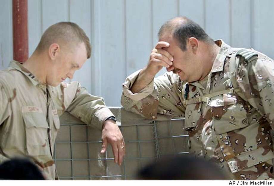 An Iraqi Civil Defense Corps commander, right, waits with a U.S. Army soldier outside of a medical facility at Camp Victory, near Abu Ghraib, Iraq, Sunday, June 20, 2004, after two ICDC soldiers were killed and six were wounded in a roadside bomb explosion near Baghdad International Airport. (AP Photo/Jim MacMilan) Photo: JIM MACMILLAN