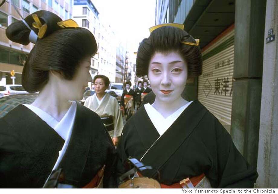 Image AAM Geisha 15:  Yoko Yamamoto, Tokyo-Past Meets Present, March 30, 2003 (Shinbashi). From the Series Tokyo Geisha, 1985-2003. C print. �yoko yamamoto. All rights reserved. From the exhibition Geisha: Beyond the Painted Smile on view at the Asian Art Museum from June 25 to September 26, 2004. This exhibition was developed by the Peabody Essex Museum, Salem Massachusetts. PERMISSION IS GRANTED TO REPRODUCE THIS IMAGE SOLELY IN CONNECTION WITH A REVIEW OR EDITORIAL COMMENTARY ON THE ABOVE-SPECIFIED EXHIBITION. ALL OTHER REPRODUCTIONS ARE STRICTLY PROHIBITED WITHOUT THE PRIOR WRITTEN CONSENT OF THE ARTIST AND/OR MUSEUM.