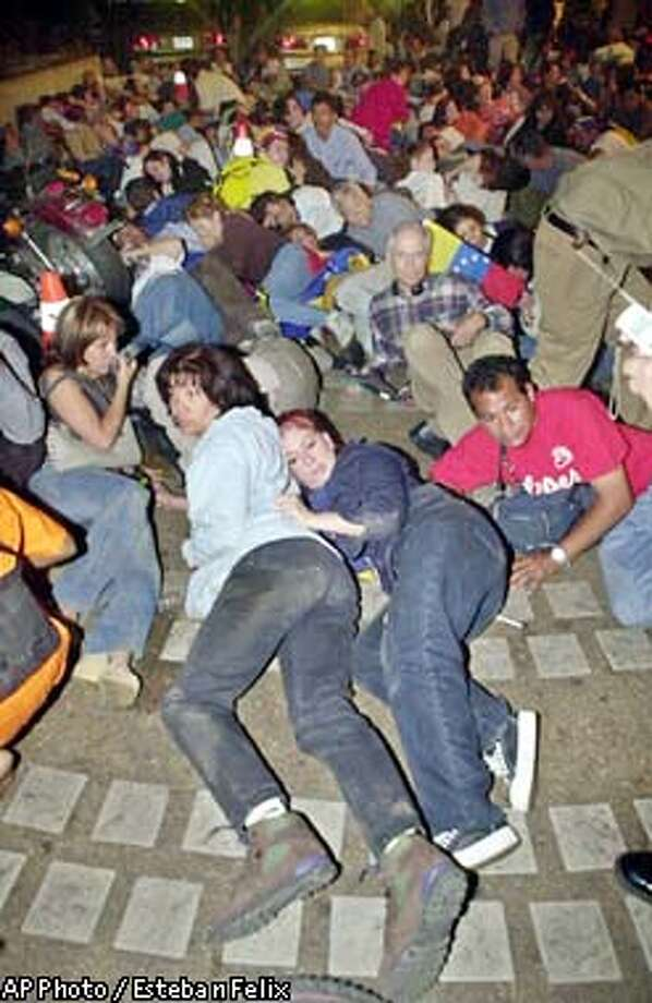 Members of the opposition take cover at the Altamira Plaza after gunmen opened fire on an opposition rally in Caracas, Venezuela, Friday, Dec. 6, 2002. (AP Photo/Esteban Felix) Photo: ESTEBAN FELIX