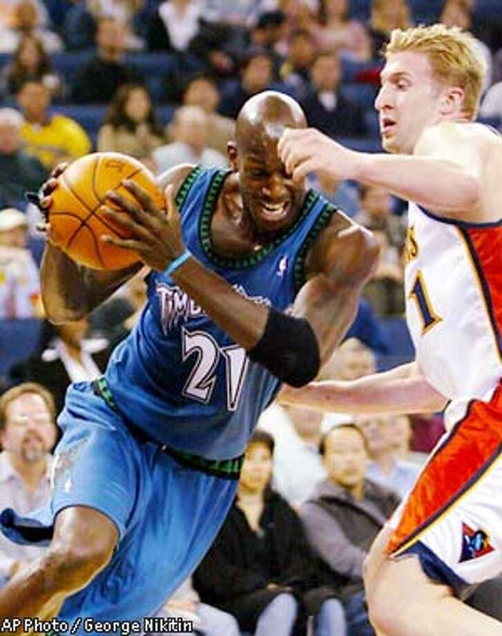 Minnesota Timberwolves' Kevin Garnett, left, drives for the basket against Golden State Warriors' Troy Murphy on Thursday, Dec. 5, 2002, in Oakland, Calif. (AP Photo/George Nikitin) Photo: GEORGE NIKITIN
