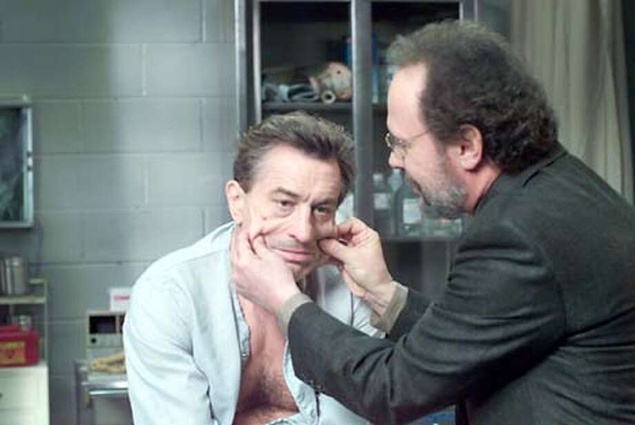 "Psychotherapist Ben Sobel (Billy Crystal, right) tries to coax mob boss Paul Vitti (Robert De Niro) out of his jailhouse stupor in ""Analyze That."""