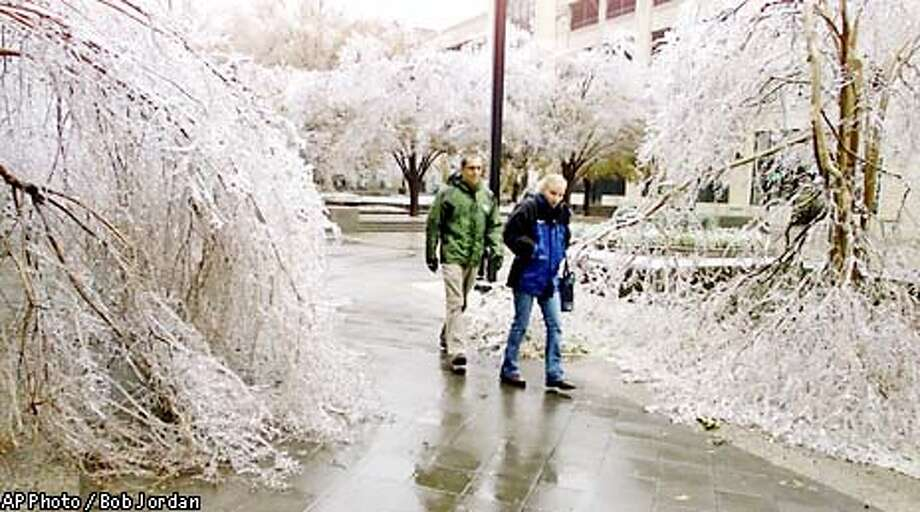 Two people walk between ice covered downed tree limbs in downtown Raleigh, N.C., Thursday, Dec. 5, 2002, after a winter strom hit North Carolina leaving more than a million people without power.(AP Photo/Bob Jordan) Photo: BOB JORDAN
