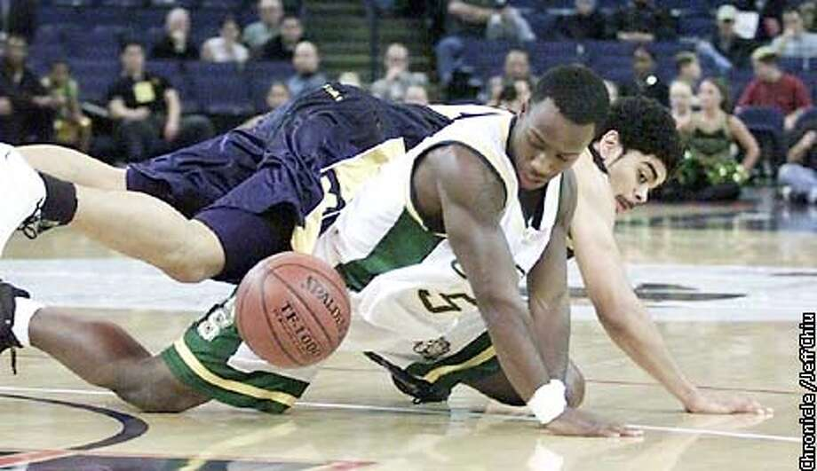 USF30B-C-29DEC01-SP-JC-- USF's Jason Gaines loses the ball as Michigan's Dommanic Ingerson falls on top of him as the Dons play the Michigan Wolverines in the first half at the Pete Newell Challenge on Saturday night at the Arena in Oakland. Photo by Jeff Chiu / The Chronicle.