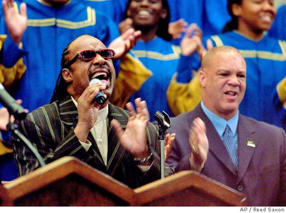 Stevie Wonder sings and the Rev. Robert Robinson Sr., son of Ray Charles, sings along, right, during funeral services for Ray Charles at First AME Church in Los Angeles Friday, June 18, 2004. (AP Photo/Reed Saxon) Photo: REED SAXON