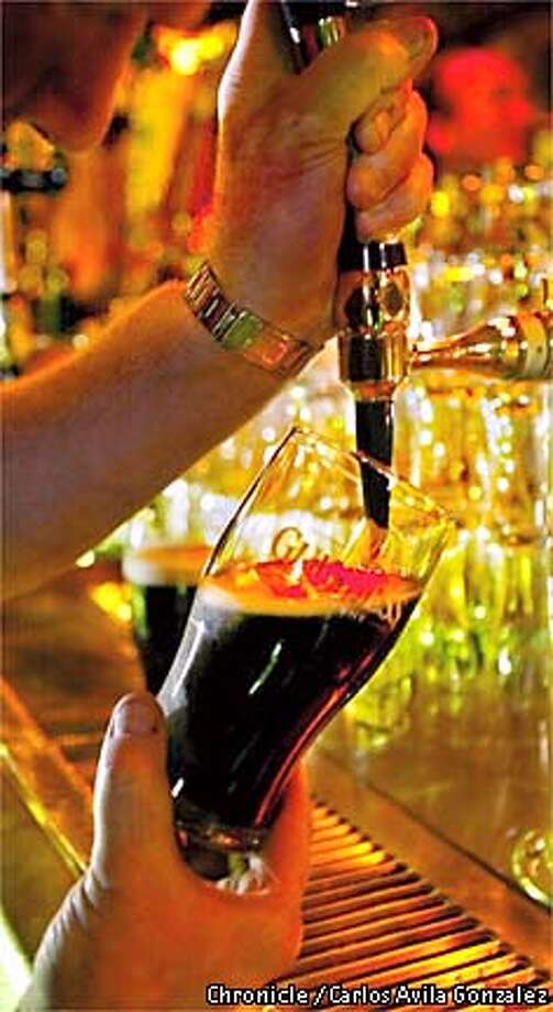 Guiness, retains its popularity during the holidays. Here, Miles O'Reilly, owner of O'Reilly's Irish Pub, pours a stout in the bar on Tuesday, November 26, 2002. (BY CARLOS AVILA GONZALEZ/THE SAN FRANCISCO CHRONICLE) Photo: CARLOS AVILA GONZALEZ
