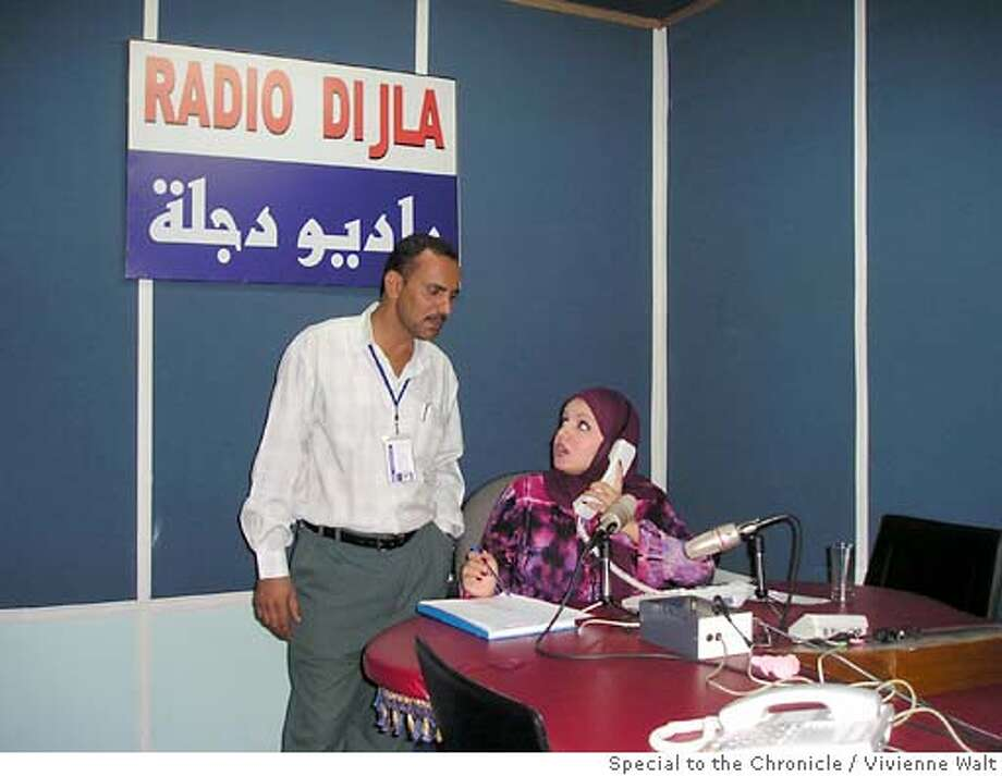 In the studio of Iraq's first pure talk-radio  station, which started six weeks ago, the youngest  presenter, 21-year-old Shama'a Al-Ameri, talks to one  of the station's senior staff, Kareem Al-Yousif,  during a break in her lunch-time show. She fields  hundreds of calls during her show from residents  complaining about life in Baghdad. (Baghdad, June 16, 2004) Photo by Vivienne Walt/SPECIAL FOR THE CHRONICLE