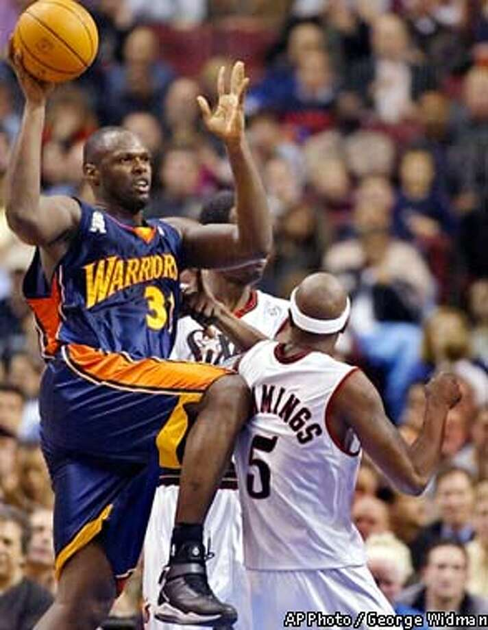 Golden State Warriors' Adonal Foyle (31) passes the ball above Philadelphia 76ers' Vonteego Cummings (5) and Jabari Smith in the first half in Philadelphia Wednesday, Feb. 20, 2002. (AP Photo/ George Widman)