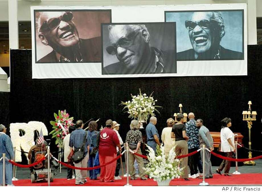 Fans of music legend Ray Charles pay respect as he lay in repose Thursday, June 17, 2004, in Los Angeles. Moments later Charles' casket was opened for public viewing. The funeral for Charles, who died Thursday June 10, is Friday.(AP Photo/Ric Francis) Photo: RIC FRANCIS