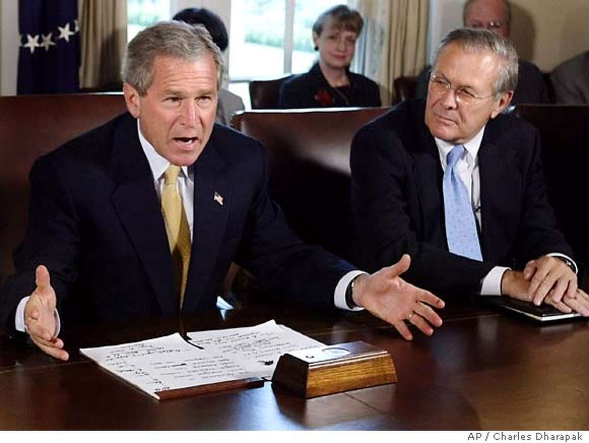 President Bush, left, speaks to reporters as Secretary of Defense Donald Rumsfeld, right, looks on at the end of a Cabinet meeting at the White House Thursday, June 17, 2004 in Washington. President Bush on Thursday disputed the Sept. 11 commission's finding that there was no