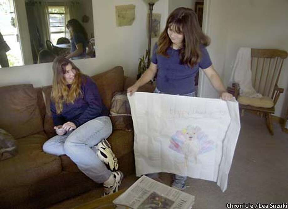 From left: Carrie Osuna and her daughter Hailey, 9. Hailey shows off her drawing to her mother in their home the day before Thanksgiving. Season of Sharing, carrie and james osuna at 493 southwood avenue, Sunnyvale. The osunas have been hit by the silicon valley bust. They have both lost their jobs and while the situation should be temporary, it has put them in a situation they are not familiar with: being in need. THEY ARE VERY SHY> DO NOT WANT TO BE DIRECTLY PHOTOGRAPHED ALTOGETHER. MOTHER MIGHT DO PICTURE WITH KIDS BUT HUSBAND IS PROBABLY A NO.  PHOTO BY LEA SUZUKI/SAN FRANCISCO CHRONICLE Photo: LEA SUZUKI